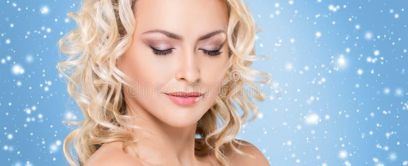 Mooi gezicht over Kerstmisachtergrond De winterportret van vrij blonde vrouw stock foto's