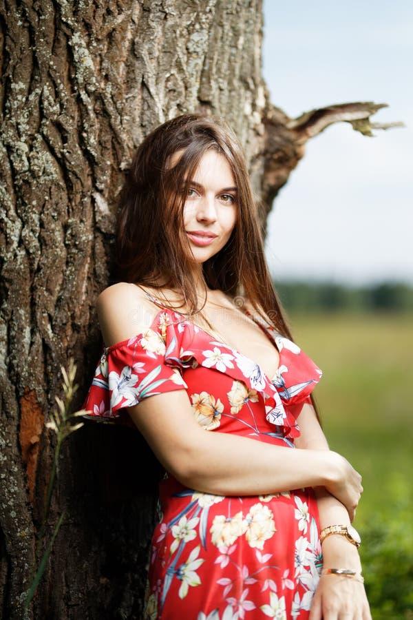 Mooi gezicht van het jonge sexy vrouw stellen dichtbij boom op aard royalty-vrije stock afbeelding