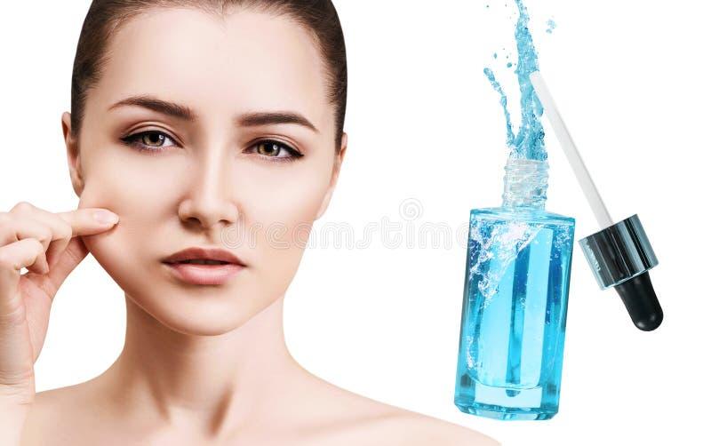 Mooi gezicht van jonge vrouw dichtbij blauwe kosmetische fles stock afbeeldingen