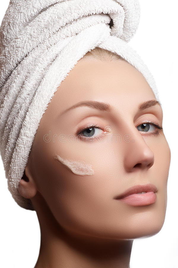 Mooi gezicht van jonge vrouw met kosmetische room op een wang stock fotografie