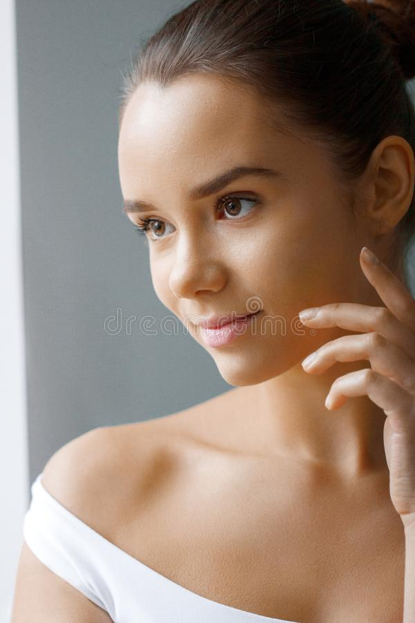 Mooi gezicht van jonge vrouw met kosmetische room op een wang De zorgconcept van de huid Close-upportret op grijze achtergrond royalty-vrije stock foto