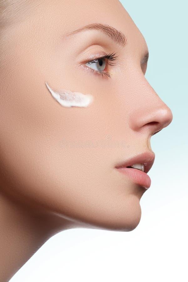 Mooi gezicht van jonge vrouw met kosmetische room op een wang De zorgconcept van de huid Close-upportret op wit Close-up stock afbeelding