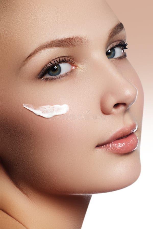 Mooi gezicht van jonge vrouw met kosmetische room op een wang Sk royalty-vrije stock foto