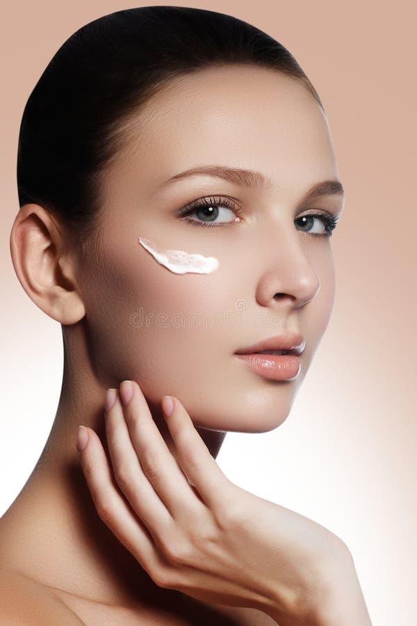 Mooi gezicht van jonge vrouw met kosmetische room op een wang Sk royalty-vrije stock fotografie