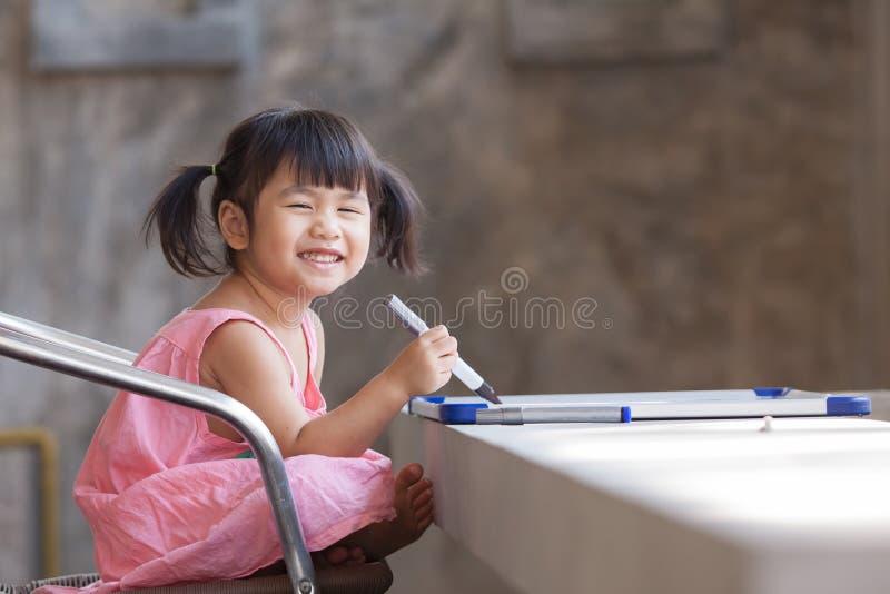 Mooi gezicht van toothy glimlachende Aziatische kinderen practive aan het schrijven royalty-vrije stock foto's