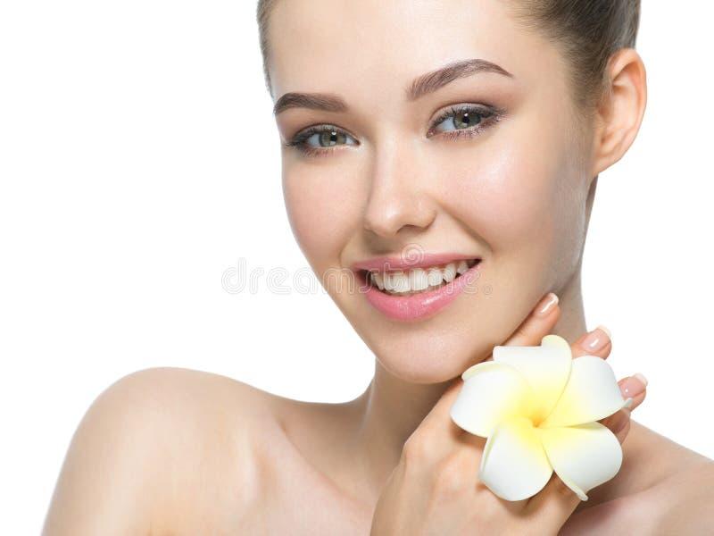 Mooi gezicht van vrolijke vrouw met bloem dichtbij gezicht stock afbeeldingen