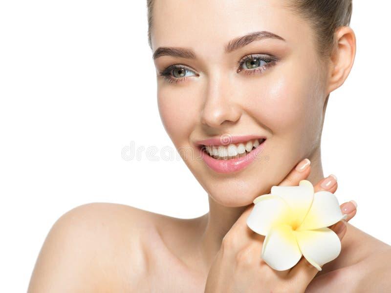 Mooi gezicht van vrolijke vrouw met bloem dichtbij gezicht royalty-vrije stock afbeeldingen
