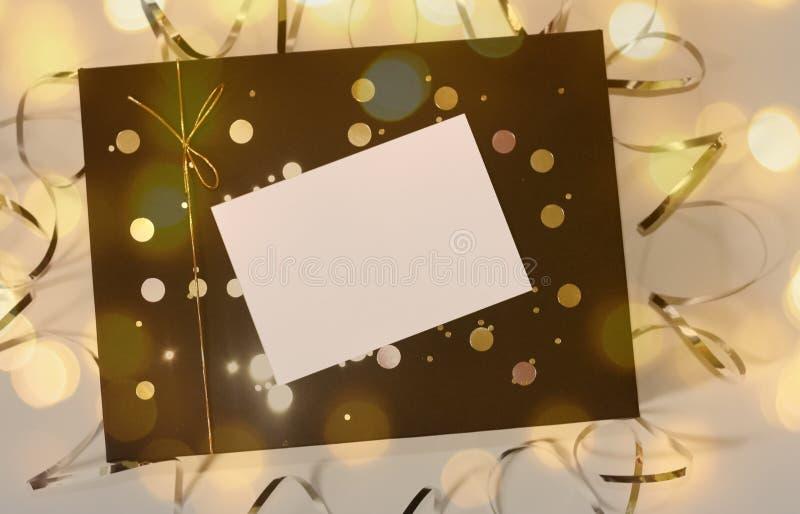 Mooi giftvakje met gouden lint en boog en lege kaart voor tekst stock afbeeldingen