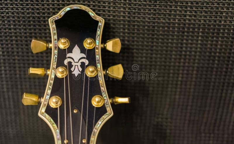 Mooi gitaarhoofd met gouden roterende knoppen en decoratief die inlegsel op een achtergrond van de muziekversterker worden geïsol stock fotografie