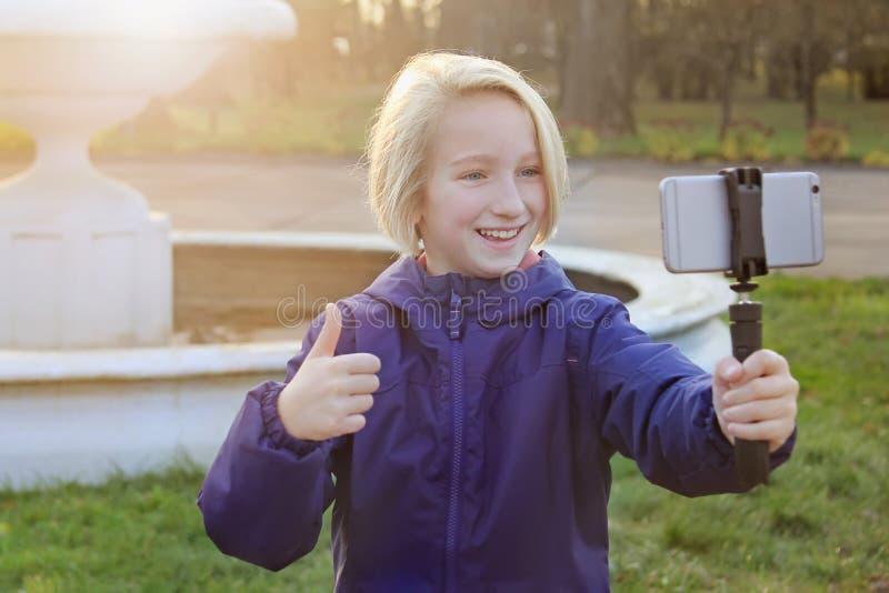 Mooi glimlachen preteen meisje 9-11 éénjarigen die een selfie in openlucht nemen Kind die een zelfportret met mobiele telefoon ne stock afbeelding