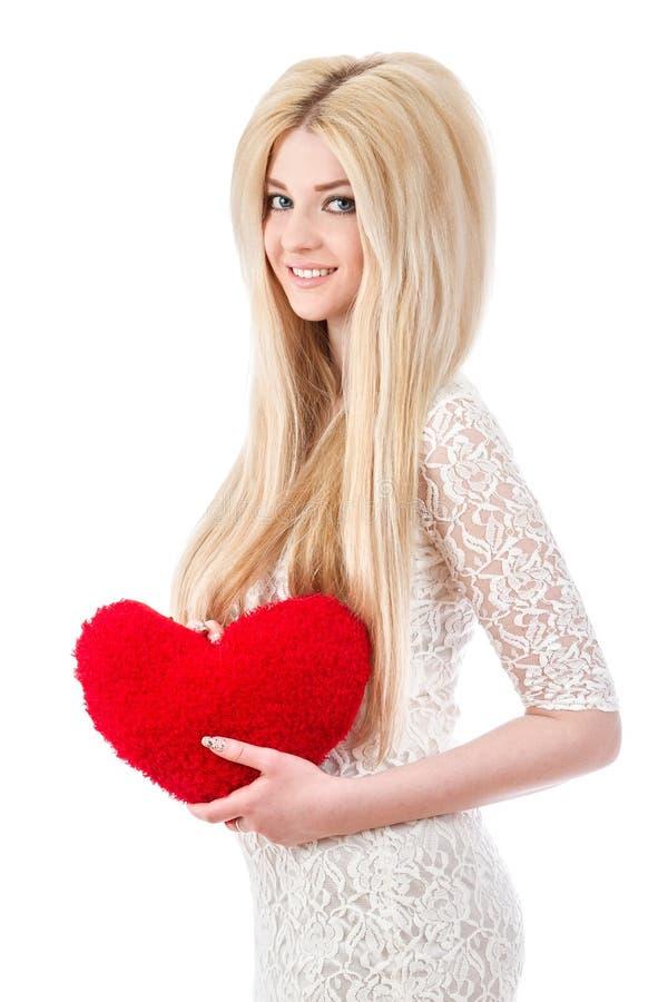 Mooi glimlachend blondemeisje met hart in handen stock afbeeldingen