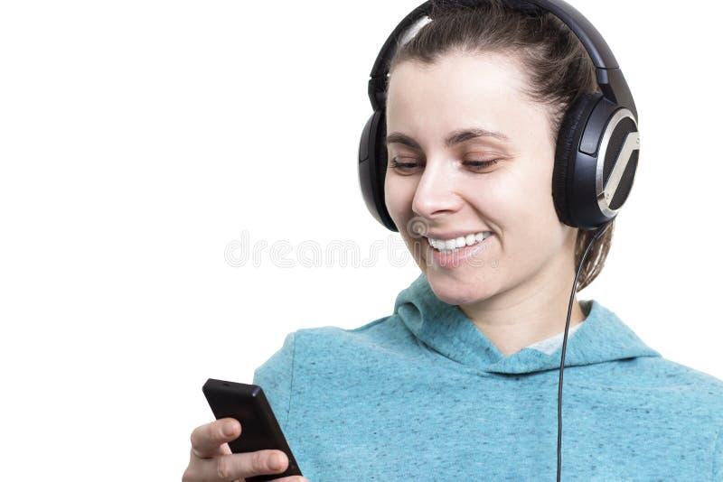 Mooi glimlachend die meisje in hoofdtelefoons met speler op witte achtergrond wordt geïsoleerd Jonge vrouw die aan muziek op de s royalty-vrije stock fotografie