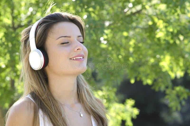Mooi glimlachend jong meisje die aan muziek luisteren royalty-vrije stock afbeelding