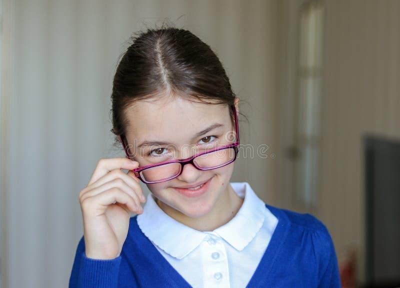 Mooi glimlachend jong schoolmeisje in het eenvormige bekijken over de bovenkant van glazen camera, close-up Terug naar School stock foto's