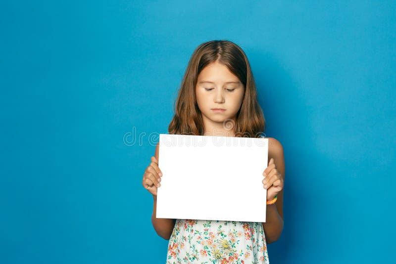 Mooi glimlachend kindmeisje die met witte tanden in ruimte van het handen de witte lege exemplaar voor de aankondiging houden royalty-vrije stock foto's