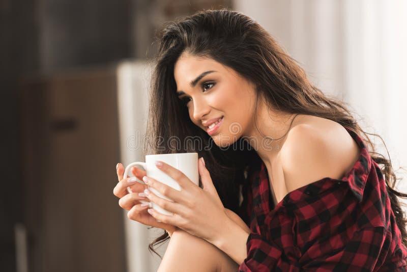 mooi glimlachend meisje in de geruite kop van de overhemdsholding van koffie en weg het kijken royalty-vrije stock foto's