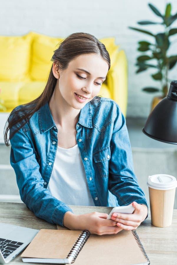 mooi glimlachend meisje die smartphone gebruiken terwijl het zitten bij bureau en het bestuderen royalty-vrije stock foto