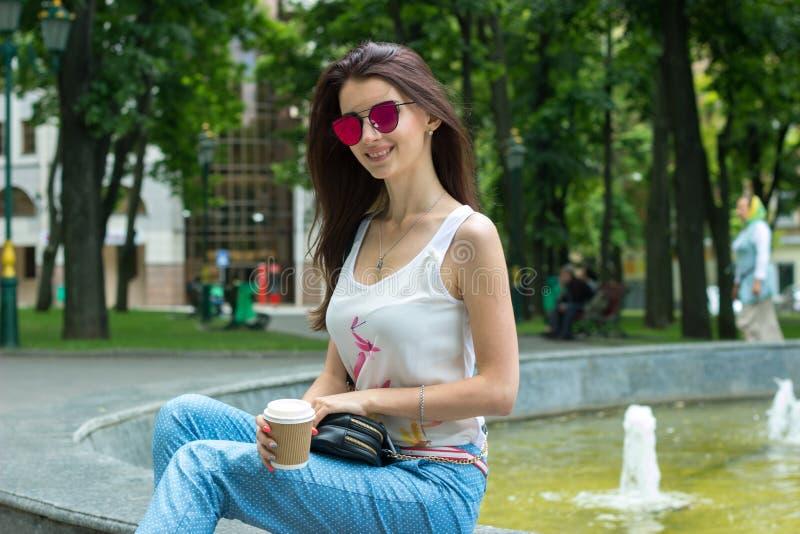 Mooi glimlachend meisje die in zonnebril dichtbij de fontein zitten royalty-vrije stock fotografie