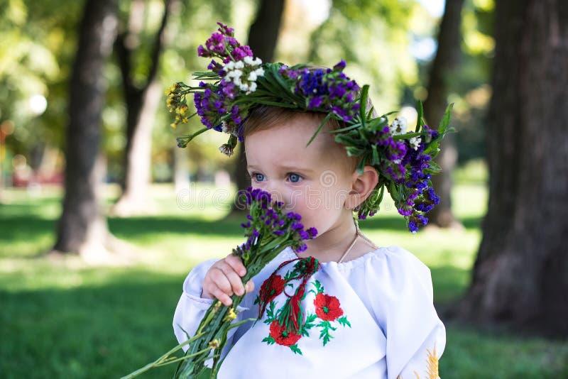 Mooi glimlachend meisje in kroon van bloemen in weide op zonnige D stock foto