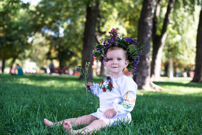 Mooi glimlachend meisje in kroon van bloemen in weide op zonnige dag stock afbeeldingen