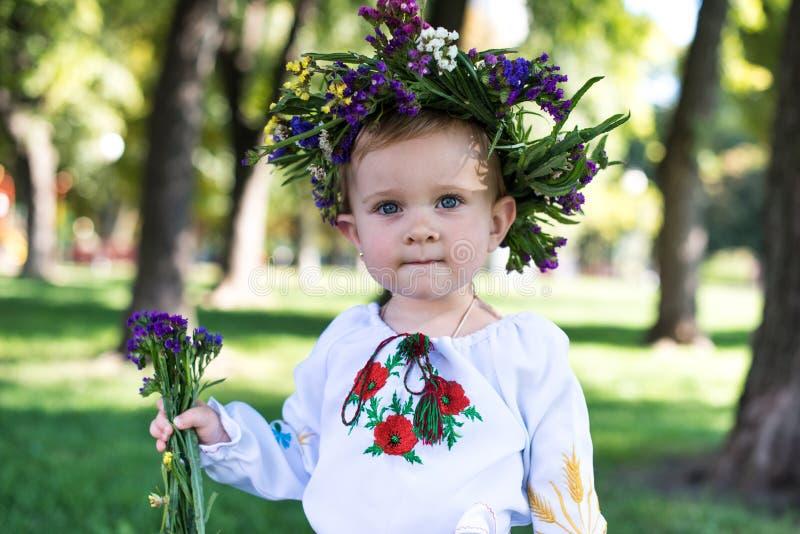 Mooi glimlachend meisje in kroon van bloemen in weide op zonnige dag stock fotografie