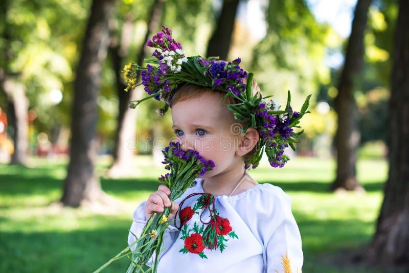 Mooi glimlachend meisje in kroon van bloemen in weide op zonnige dag royalty-vrije stock foto