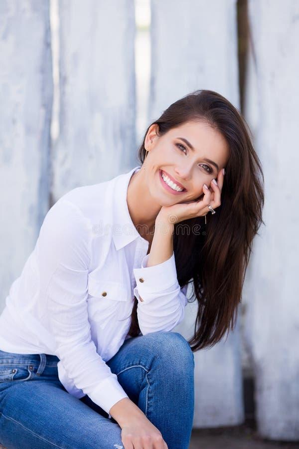 Mooi glimlachend meisje leeg wit overhemd dragen en jeans die tegen straat houten muur stellen Minimalistische stedelijke kleding stock afbeeldingen