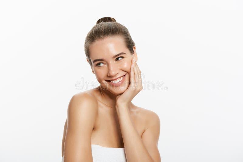 Mooi glimlachend meisje met schone huid, natuurlijke samenstelling, en witte tanden op grijze achtergrond royalty-vrije stock afbeeldingen