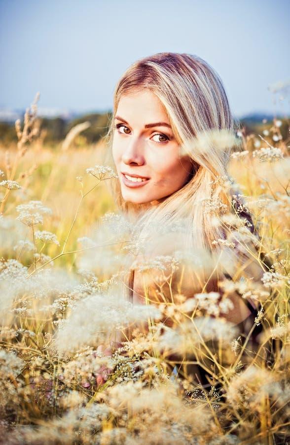 Mooi glimlachend meisje onder het gras en de bloemen stock afbeeldingen