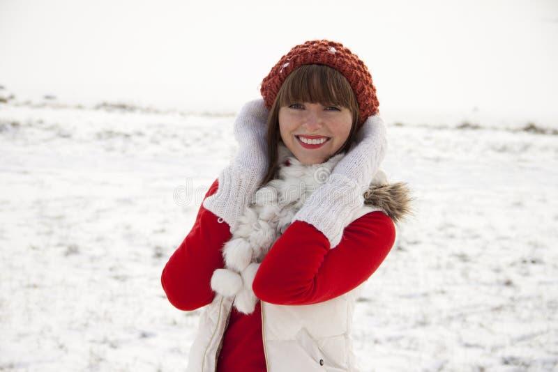 Mooi glimlachend meisje op de winterachtergrond stock afbeelding