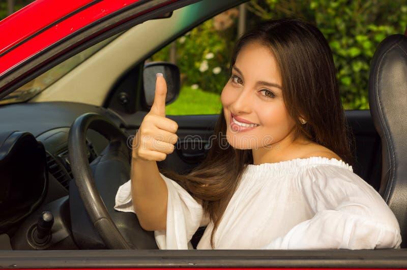 Mooi glimlachend meisje in rode auto met duimen op signaal van overwinning stock afbeelding