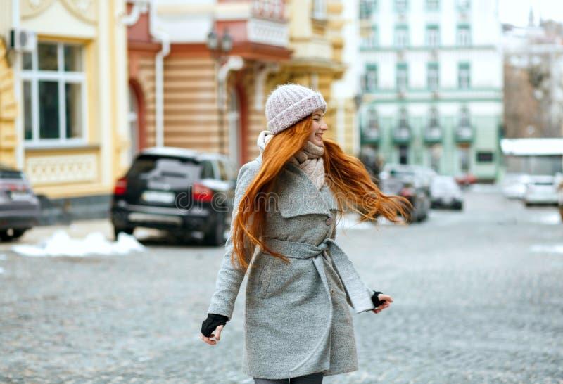 Mooi glimlachend rood haired meisje die modieuze de winteruitrusting dragen wal royalty-vrije stock foto