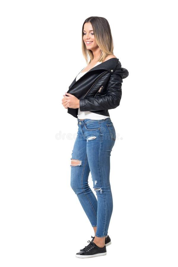 Mooi glimlachend schuw toevallig meisje die leerjasje, gescheurde jeans en zwarte tennisschoenen dragen die neer eruit zien royalty-vrije stock afbeeldingen