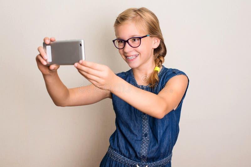 Mooi glimlachend tienermeisje die in glazen selfie foto op slim maken royalty-vrije stock afbeelding