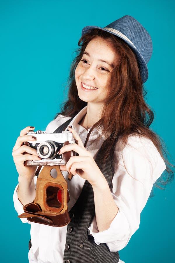 Mooi grappig freckled tienermeisje, 17-18 jaar oud, met retro camera in haar die handen, op blauwe achtergrond in studio worden g stock afbeelding