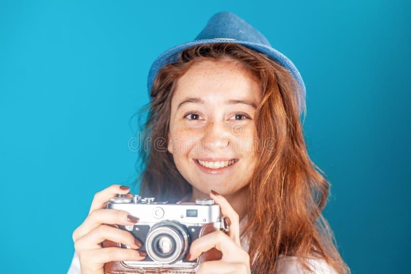Mooi grappig freckled tienermeisje, 17-18 jaar oud, met retro camera in haar die handen, op blauwe achtergrond in studio worden g royalty-vrije stock afbeeldingen