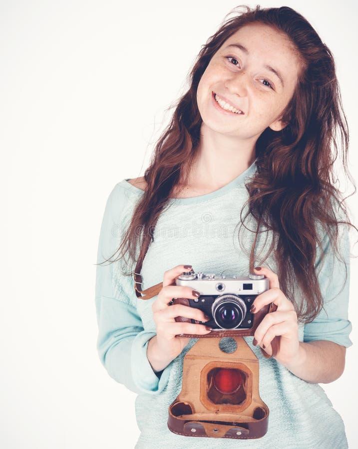 Mooi grappig freckled tienermeisje, 17-18 jaar oud, met retro camera in haar die handen, op witte achtergrond worden geïsoleerd stock fotografie