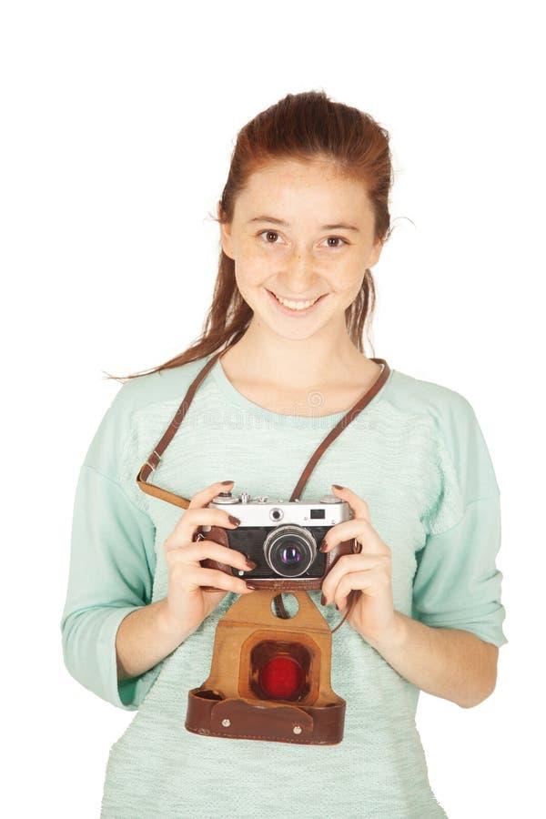 Mooi grappig freckled tienermeisje, 17-18 jaar oud, met retro camera in haar die handen, op witte achtergrond worden geïsoleerd royalty-vrije stock foto