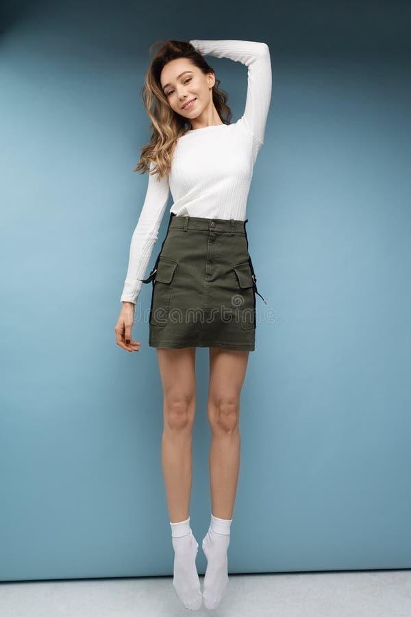 Mooi grappig meisje die in witte t-shirt groene rok en witte sokken op blauwe achtergrond springen stock fotografie
