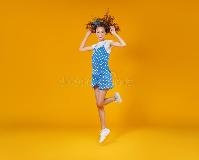 Mooi grappig meisje op gekleurde gele achtergrond stock fotografie