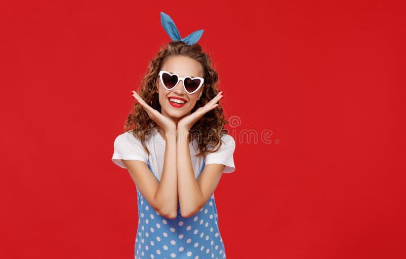 Mooi grappig meisje op gekleurde rode achtergrond stock afbeelding
