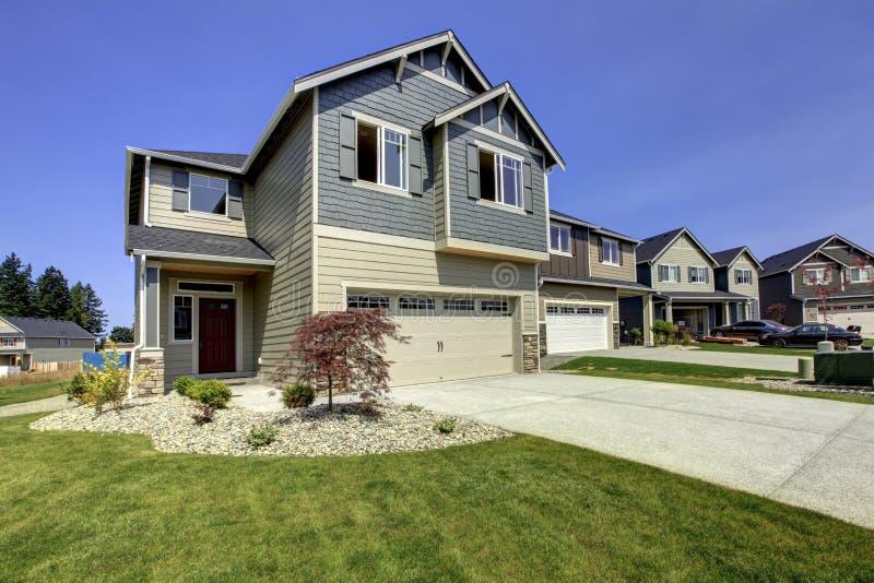 Mooi grijs huis buiten met steen, groene gazon en oprijlaan royalty-vrije stock foto