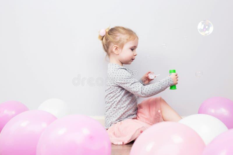 Mooi heeft weinig blondemeisje, gelukkig pret vrolijk het glimlachen gezicht, roze kleding, zeepbelventilator Portret met roze en stock fotografie