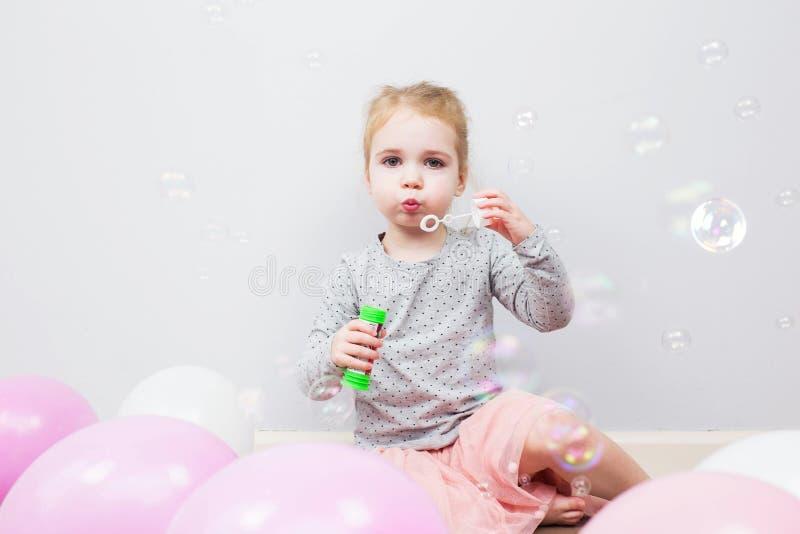 Mooi heeft weinig blondemeisje, gelukkig pret vrolijk het glimlachen gezicht, roze kleding, zeepbelventilator Portret met roze en stock foto's