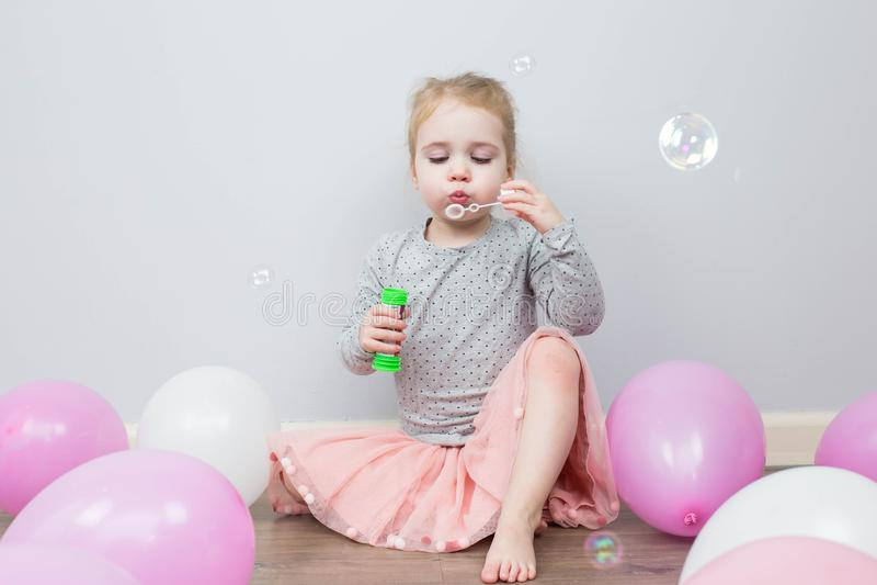 Mooi heeft weinig blondemeisje, gelukkig pret vrolijk het glimlachen gezicht, roze kleding, zeepbelventilator Portret met roze en royalty-vrije stock foto's