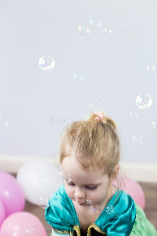Mooi heeft weinig blondemeisje, gelukkig pret vrolijk het glimlachen gezicht, roze kleding, zeepbelventilator Portret met roze en stock afbeelding