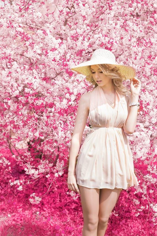 Mooi helder glimlachend zacht zoet meisje met lang blond krullend haar die een hoed met grote gebieden in de zomer roze sundress  royalty-vrije stock afbeelding