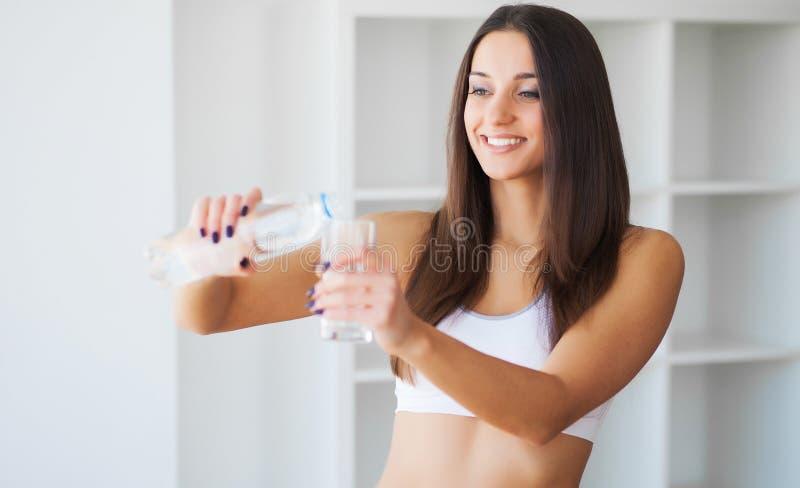 Mooi het glimlachen het glaswater van de vrouwendrank in de ochtend stock afbeelding