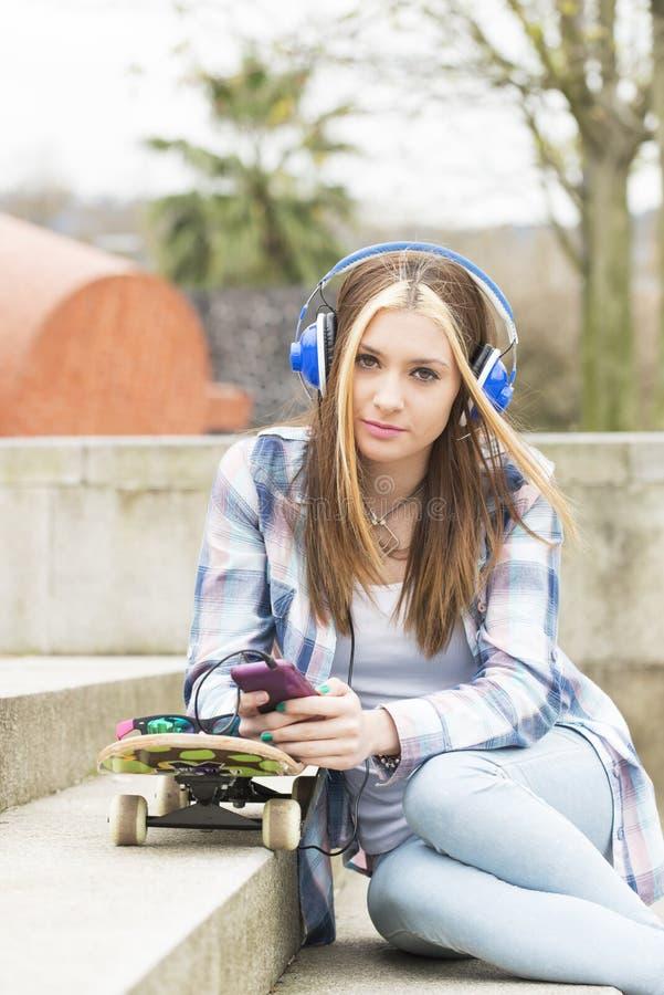 Mooi hipstermeisje met telefoon en skateboard in de straat royalty-vrije stock foto's
