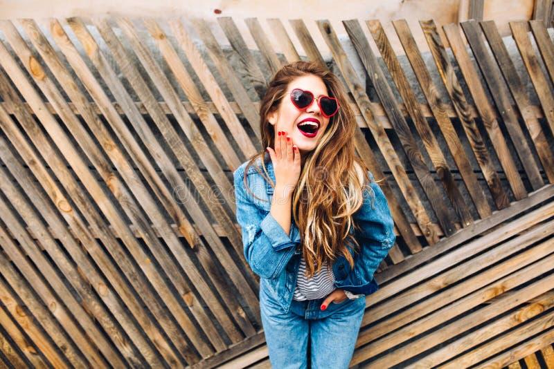 Mooi hipstermeisje in modieuze glazen die met verraste en opgewekte uitdrukking op gezicht stellen Mooie jonge vrouw met rood stock afbeelding